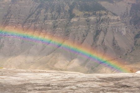 Landscape of a rainbow over the moon like terrain of the Mammoth Springs, Wyoming, USA.