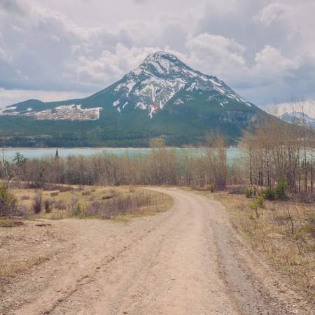 Landscape of dirt road leading to a snow capped Mount Baldy and Barrier Lake in Kananaskis Alberta. Stock Photo