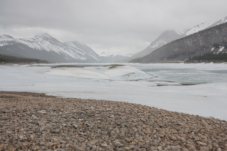 Icy Landscape with a rocky foreground at Spray Lake Reservoir, Kananaskis, Alberta.