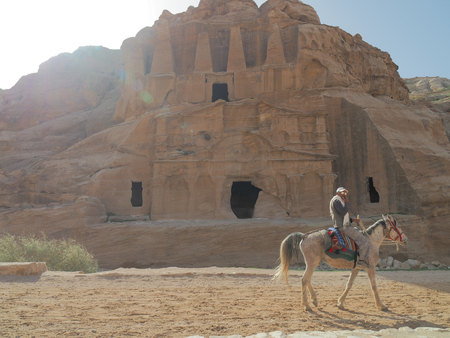 Petra, Jordan - March 7th, 2018: Local guide rides horse around Patre city. Editorial