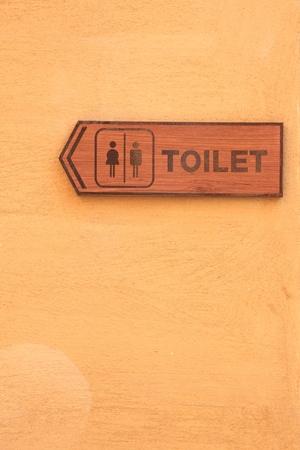 restroom sign: Toilet wood label on orange wall.