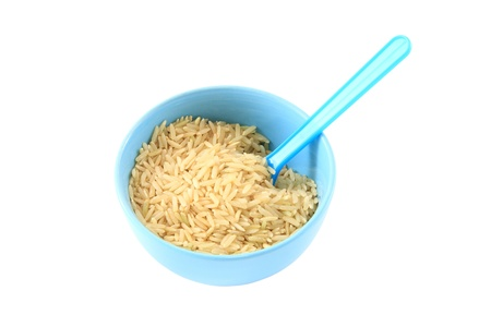 Brown rice in blue bowl. Stock Photo