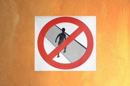 do not cross: No cruce s�mbolo en la pared de color naranja. Foto de archivo