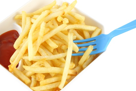 French fries with red ketchup and blue spoon on white background