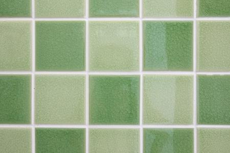 Green tone mosaic tiles glossy bathroom wall. photo