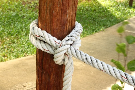 Tight rope knot close wooden pole on blur field background photo