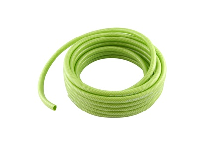 Roll of green pvc garden hose on white background.