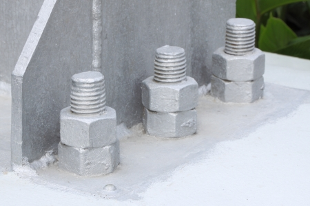 strong base: Bolt and nut of base metal pillar focus near bolt. Stock Photo