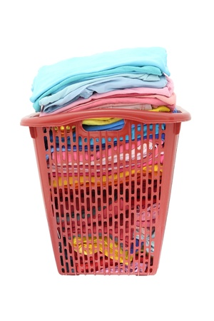 Used cloths in old red plastic basket on white background. photo