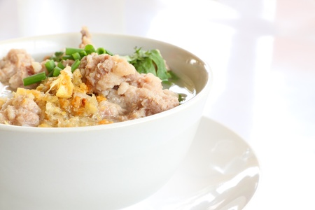 Pork congee and fried garlic on table.