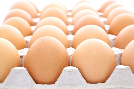 Raw eggs contained carton box focus near on white background.
