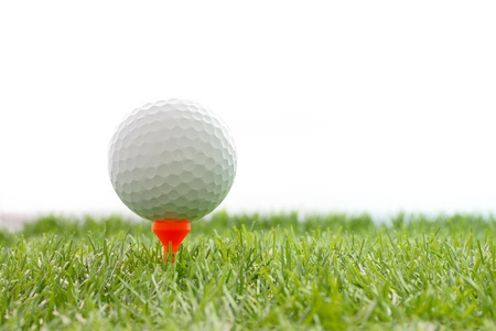 Golf ball on plastic tee in green grass.