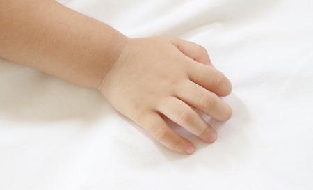 main Retour de bébé asiatique sur boutis blanc.