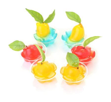 Group of deletable imitation fruits in jelly cup on white floor. Stock Photo