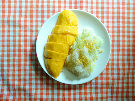 Mango with Sticky Rice, Thai dessert on orange checkered tablecloth background