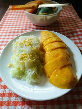 Mango with Sticky Rice, Thai dessert on orange checkered tablecloth background