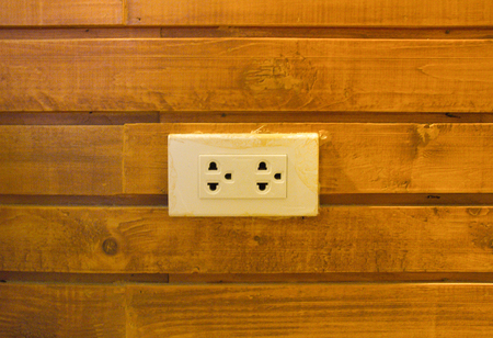 electric plug outlet on the wall wooden background Stockfoto
