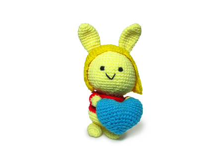 Cute Handmade Crochet Yellow Doll Hand Holding Blue Heart isolated on white background with Clipping Path Stock Photo
