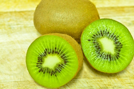 Whole kiwi fruit and his sliced segments isolated on white background cutout photo