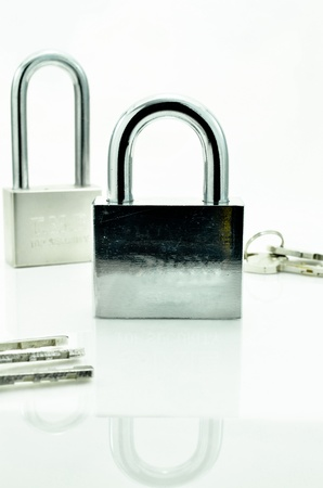 Closed padlock with key on a white background with reflections photo