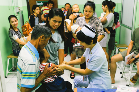 inyeccion intramuscular: CHIANG MAI, Thailand - August 7, 2016: Mother and her Child receiving vaccine at out side of the thigh.Children vaccine in hospital . CHIANG MAI, Thailand. Editorial
