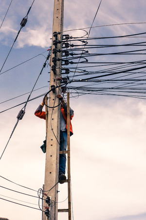 essentially: Bangkok, Thailand: Worker climbing on transmission line tower. Un-safety condition. Stock Photo