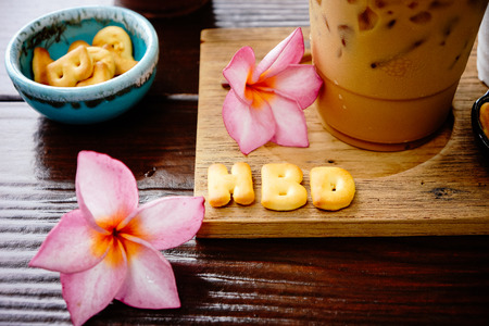 iced coffee and biscuit alphabet spell HBD with rice field background Stock Photo