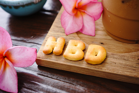 water alphabet: iced coffee and biscuit alphabet spell HBD with rice field background Stock Photo
