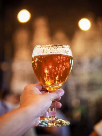 degustating: hand holding glass of draft lager beer Stock Photo
