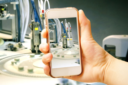 manual test equipment: Hand holding smart phone (Mobile Phone) with centrifuge. advanced laboratory equipment Stock Photo