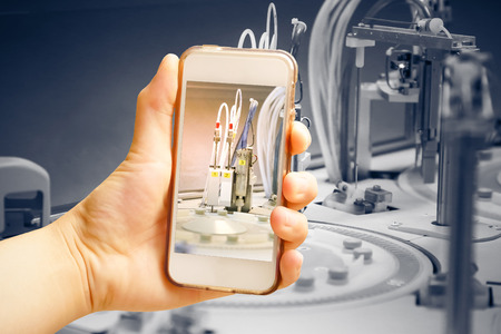 Hand holding smart phone (Mobile Phone) with centrifuge. advanced laboratory equipment Stock Photo