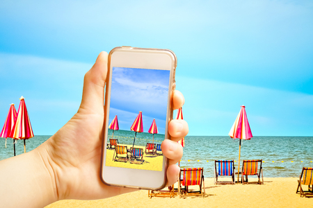 Hand holding smart phone (Mobile Phone) with Chairs and umbellar on white sand beach.