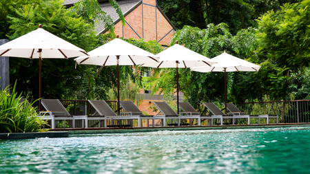 Empty poolside loungers with umbrellas