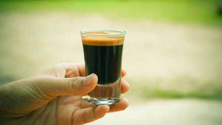 Hand holding a glass of expresso coffee