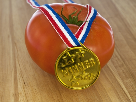 tomato with a gold medal winner pendant on a wooden background photo