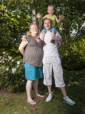 happy family with pregnant mother with toddler in a garden photo