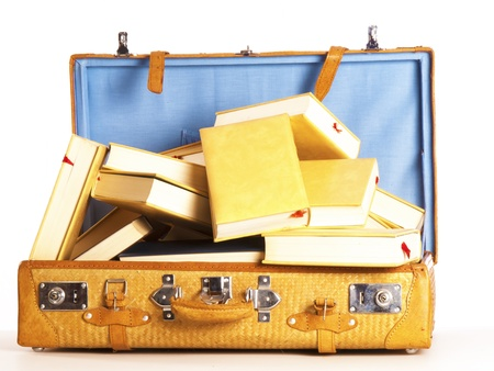 a travel suitcase full of books on a white background Stock Photo