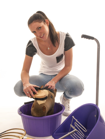beautiful girl with horses cleaning equipment photo