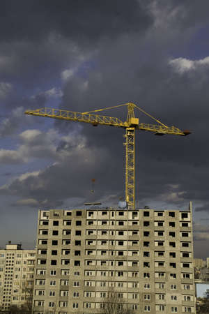 erecting: Hoisting crane lifting a concrete slab on a house being built, on the background of gloomy thunder clouds Stock Photo