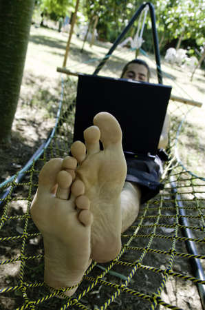 Young barefoot man lying in hammock surfing Internet in shade of tropical trees