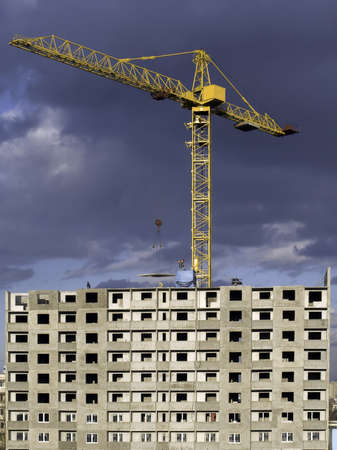 Hoisting crane lifting a concrete slab on a house being built, on the background of gloomy thunder clouds photo