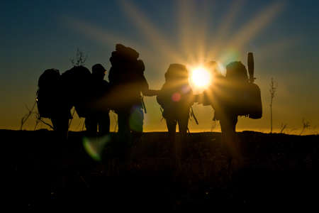 Silhouettes of hikers walking in sunset with sunbeams and reflections