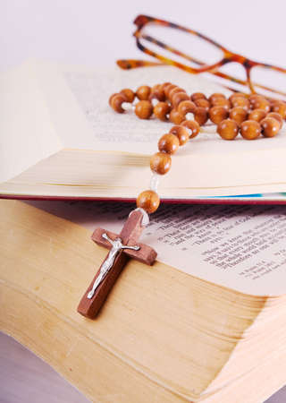 Open Holy Bible lying on stack of old books with glasses, cross and beads photo