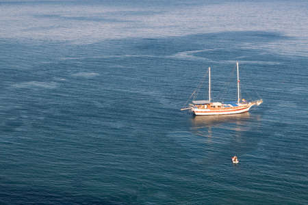 Sailboat at anchor on calm sea with lowered sails and small motorboat approaches the sailboat, shot from above, with copyspace photo