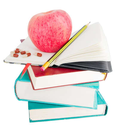 stimulate: Apple with pills and pencil on textbook heap as ways to stimulate memory