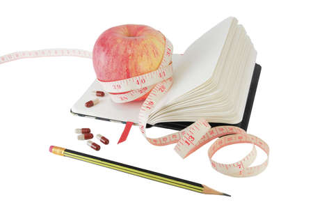 Copybook with apple, measure tape and vitamin pills to aid effective diet photo