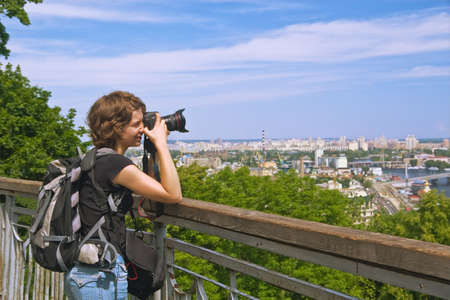 Pretty young woman with photocamera and backpack shooting the city of Kyiv from the hilltop photo