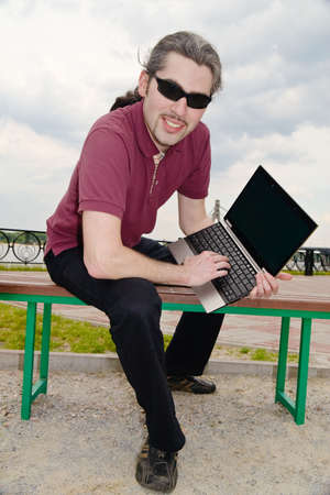 Young man sitting on a park bench with his laptop photo