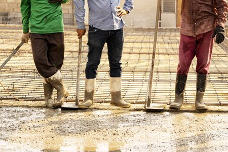Three workers extended their breaks beside wet concrete.