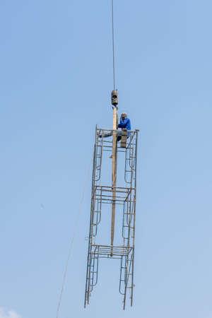 Crane has raised steel scaffoldind whick worker sitting on the wood plate. 版權商用圖片